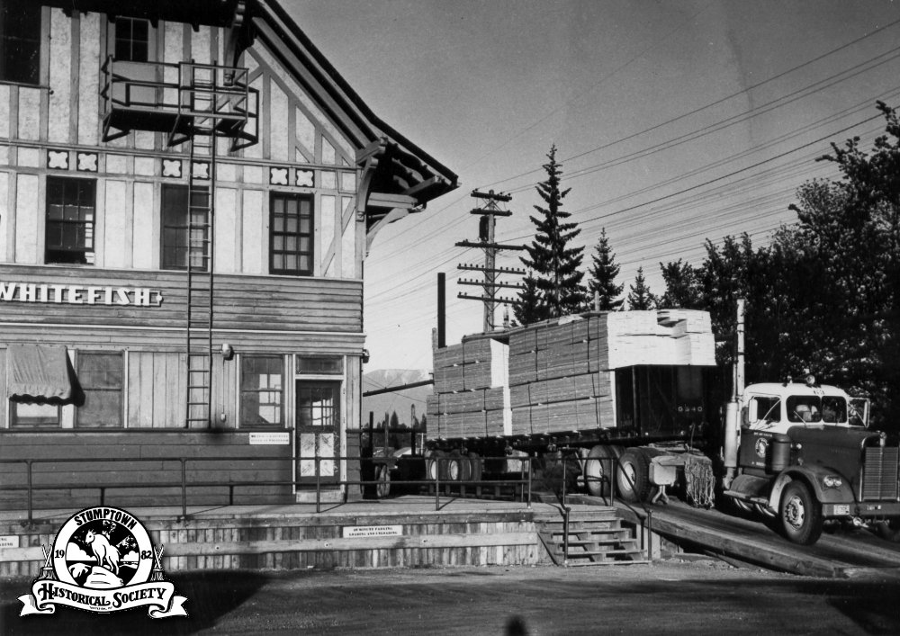 Kenworth tractor with Great Northern bulkhead loaded with Whitefish lumber, 1961.